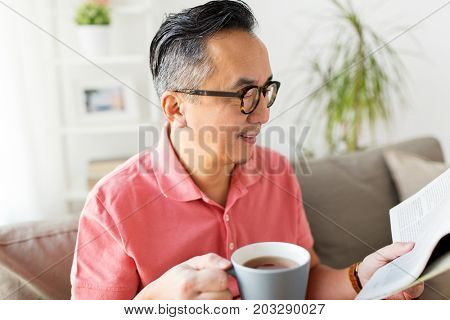 leisure, information, people and mass media concept - happy man in glasses reading newspaper and drinking coffee at home