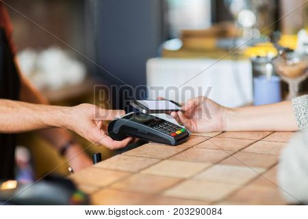 modern technology and people concept - man or bartender with payment terminal and customer with smartphone at bar of coffee shop