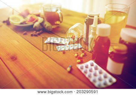 health, traditional medicine and ethnoscience concept - natural and synthetic drugs on wooden table