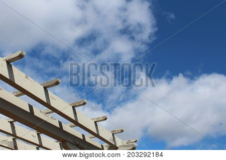 Edge of a pergola against a blue sky with clouds, horizontal aspect