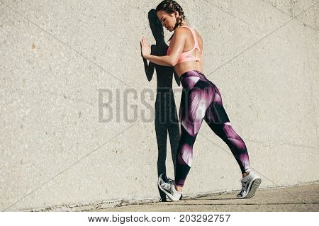 Fit young woman doing stretching workout against a wall. Fitness female exercising in morning outdoors.