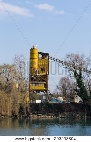 Stone quarry with yellow silo and conveyor belt. Industrial equipment. Mining