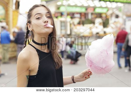 Pretty Brunette Girl Eating Cotton Candy.