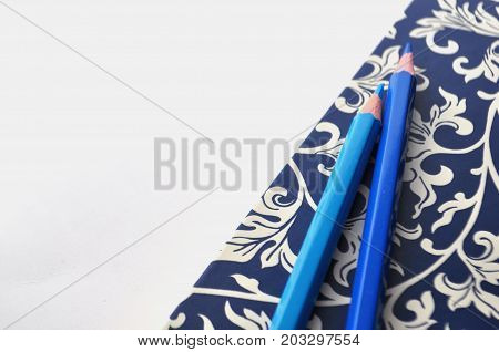 Styled blue floral notebook with blue gold pencil on blue background with text space