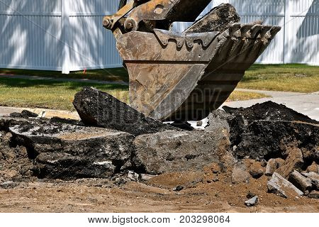 An excavating bucket scoops up a load of asphalt chunks in a street construction project