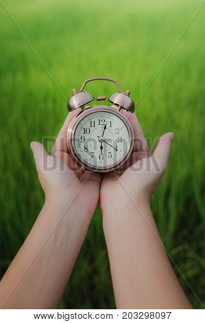 Retro alarm clock or vintage alarm clock in hand on green natural backgroundTime