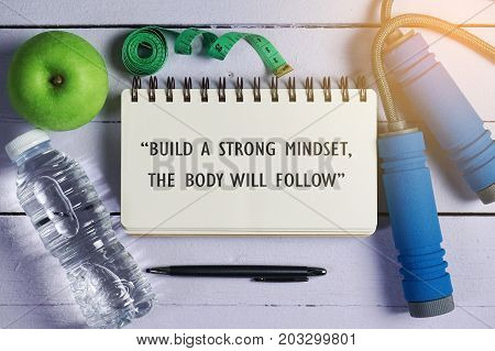 Fitness Concept. Top view of water, green apple, measuring tape, jumping rope, pen and open notebook written with fitness quotes over wooden background. Build a strong mindset, the body will follow.