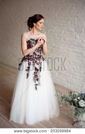 Full-length portrait of Beautiful luxurious female model with medium brown hair in a long fashinable dress standing in the room. Bridal clothes concept. Stylish wedding dress.