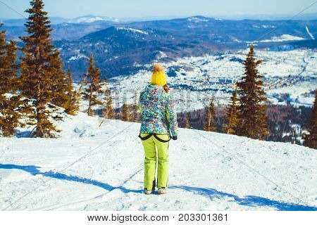 Hiker woman standing with hands up achieving the top admiring winter mountain landscape.