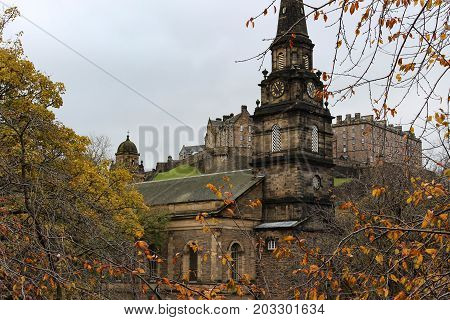 View of Edinburgh Castle and St. Cuthbert's Church from Princes Street Garden in Edinburgh Scotland in the autumn or early winter.