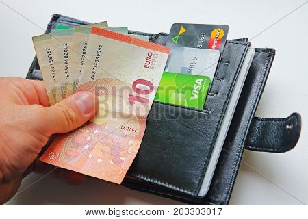 Berlin Germany - September 4 2017: Money euro banknotes in hand against wallet with bank cards Visa and MasterCard close-up. Finance and money concept.