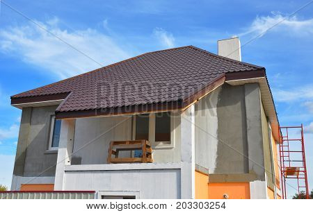 Construction or repair of the rural house with balcony eaves windows chimney roofing fixing facade insulation plastering and painting walls. Painting House Facade Wall. Roofing.