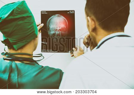 Doctors Looking At X-ray Film Of Patient 's Head