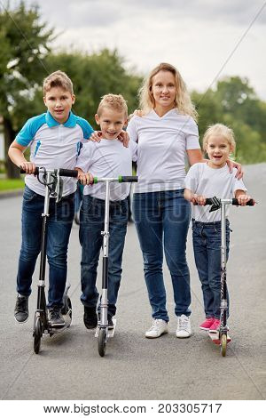 Woman and three children on scooters stand on road.