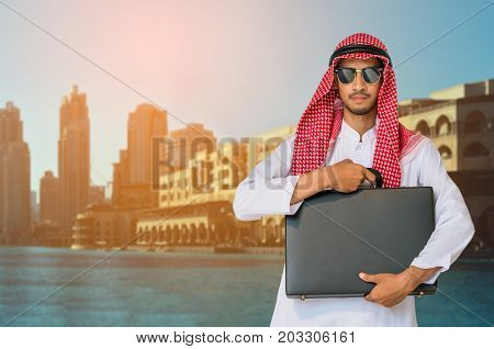 Arab man holding business briefcase in modern city. Concept of overseas international business of Arab businessman.