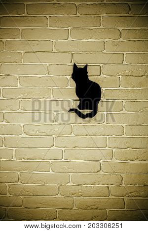 Halloween black cat silhouette paper cutout on beige brick wall. Mystery and superstition concept. Holiday celebration symbol copy space