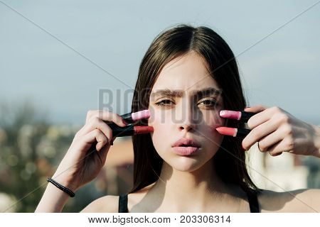Model Posing With Pink Lips And Lipsticks On Blue Sky