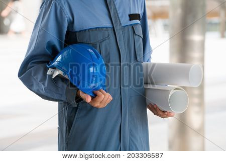 Engineer on professional wear holding hard hat and blueprint drawing. Engineering people concept.