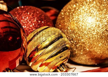 Red and yellow shimmering christmas baubles. Symbolic objects. Xmas decoration. Retro photo filter.