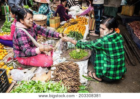 Nyaungshwe Myanmar - 2017 January 4 : A female hawker or vendor selling tamarind to a female customer both wearing thanaka cream in a street market in the town of Nyaungshwe on the Inle Lake of central Burma