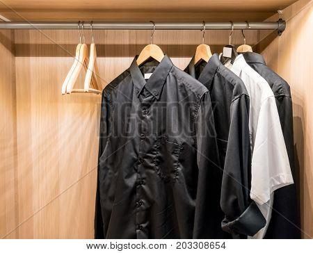 Black Basic Shirts Hanging In The Closet.