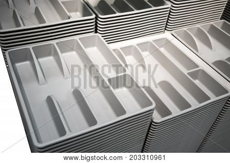 Stacks and Rows of grey plastic cutlery tray. Easy to fit in kitchen drawer for sorting spoon fork and other
