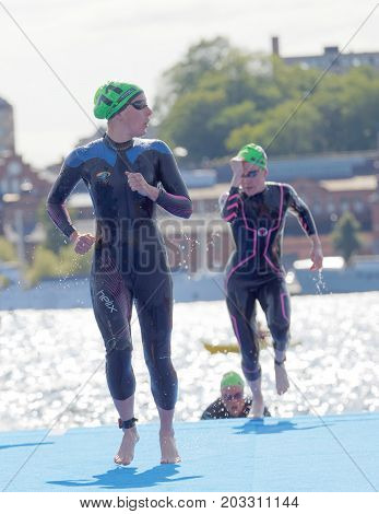 STOCKHOLM - AUG 26 2017: Group of female triathlete swimmers wearing black swimsuits running up from the water in the Women's ITU World Triathlon series event August 22 2017 in Stockholm Sweden