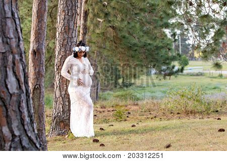 Beautiful Pregnant Woman In White Lace Maternity Dress Outdoors In Field - Looking Down At Baby Bump