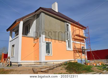 Construction or repair of the rural house with balcon eaves windows chimney roofing fixing facade insulation plastering and using color. House construction.