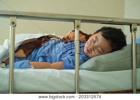 Sick Asian kid boy 2 years old lying sick in hospital bed. dim light selective focus.