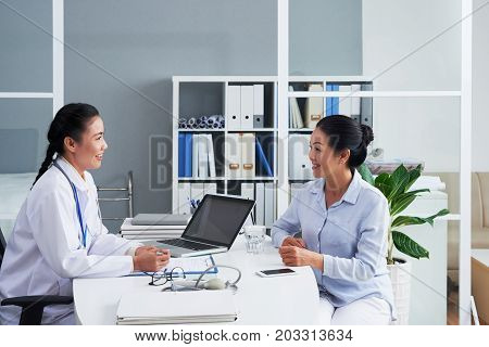 Smiling Asian doctor consulting senior female patient