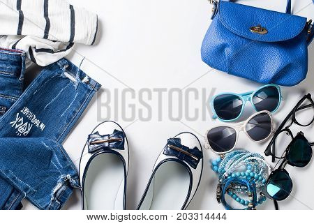 Collage of Feminine clothing and accessories in a marine style on white background.
