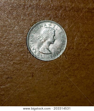 An Old Six Pence Penny Silver Coin With A Background Table Top Wood