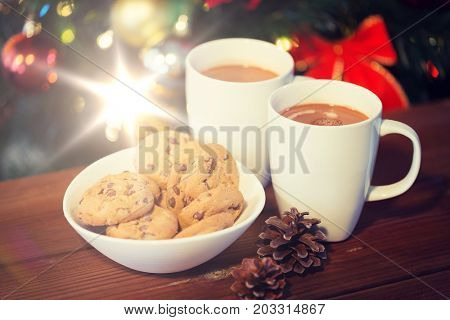 holidays, winter, food and drinks concept - close up of oatmeal cookies, cups with hot chocolate or cocoa drink and pinecones on wooden table over christmas tree background