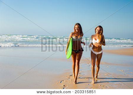 Best friends enjoying the summer, running on the beach with a surfboard