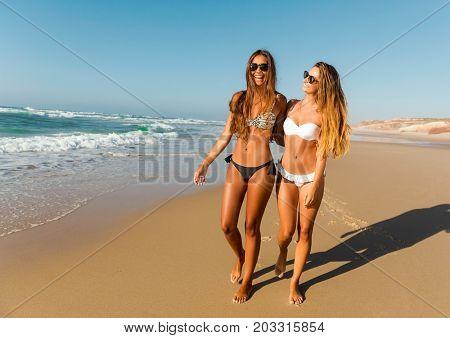 Beautiful girls walking and having fun on the beach