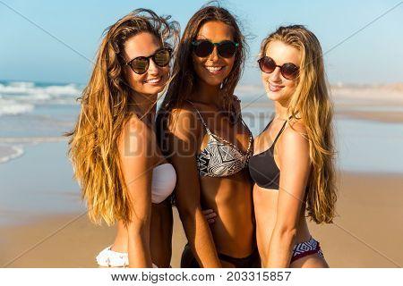 Three beautiful girls having fun on the beach