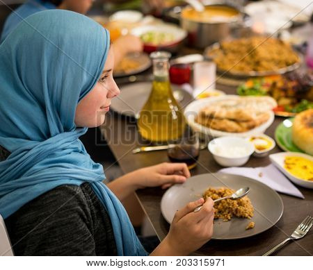 Muslim girl having dinner at home with her family