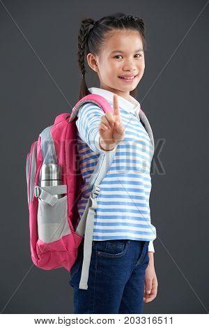 Portrait of smiling Asian schoolgirl showing index finger