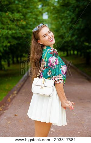 Young happy woman in white skirt and flowers blouse in the summer park