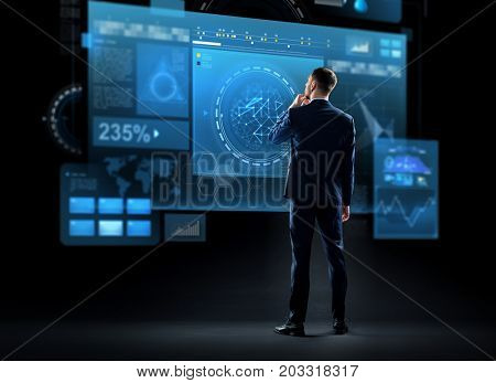 business, technology and people concept - businessman in suit looking at virtual screen over black background from back