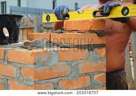 A bricklayer using a level to check his new wall outdoor