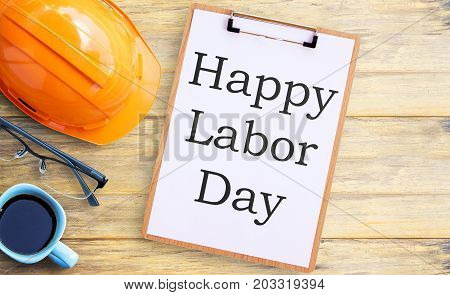 Top view with orange safety helmetglassesclipboard and cup of coffee on old wooden table background. space for use and any design. Business and labor day concept.