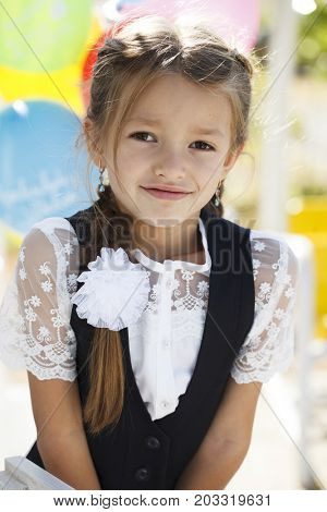 The first of September is the day of knowledge. Portrait of a beautiful first-grader girl in school uniform
