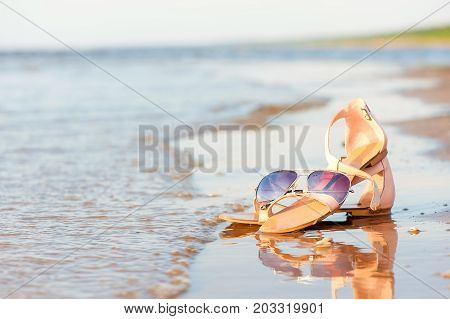 Fashionable women sandals and sunglasses on summer sandy wet coastline. Outdoors image.