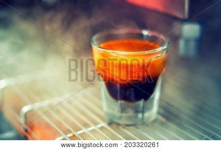 Close-up Shot Of A Glass With Freshly Brewed Espresso On A Coffee Machine
