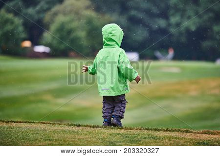 back view of the boy walking the golf course