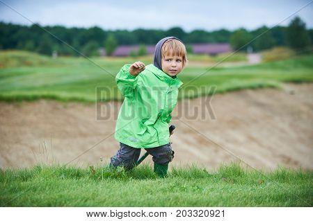 little boy walking the green golf course