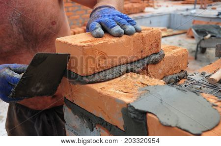 A closeup of a bricklayer worker installing red bloks and caulking brick masonry joints exterior wall with trowel putty knife outdoor.
