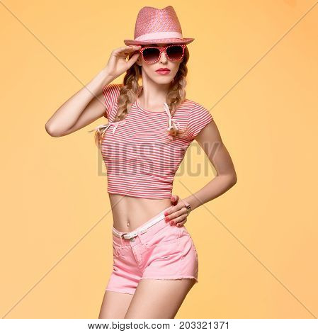 Fashion Hipster woman Cheeky emotion. Stylish Pink Outfit. Sexy Blond Model Crazy Girl, Fashion Sunglasses, Glamour Pink Shorts, Top. Trendy pink fashion Hat. Playful Summer Hairstyle